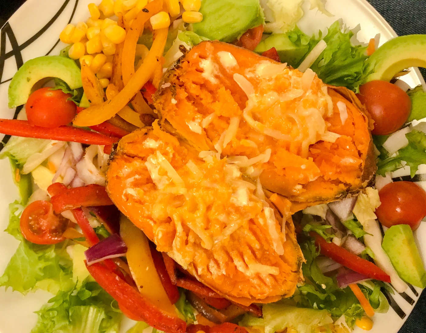 Rainbow salad with buttered sweet potato, salad leaves, tomatoes, avocado, sweetcorn, peppers and onion