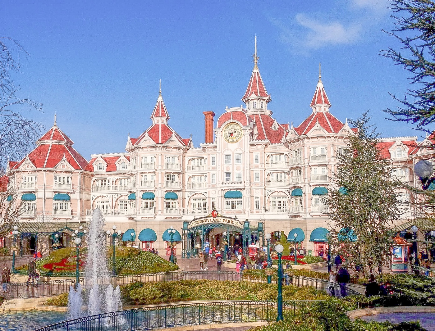 Disneyland Paris Magic Kingdom entrance with fountains, greenery and buildings