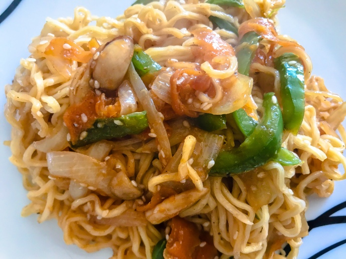 Sweet and sour noodles with stir fried vegetables and sesame seeds