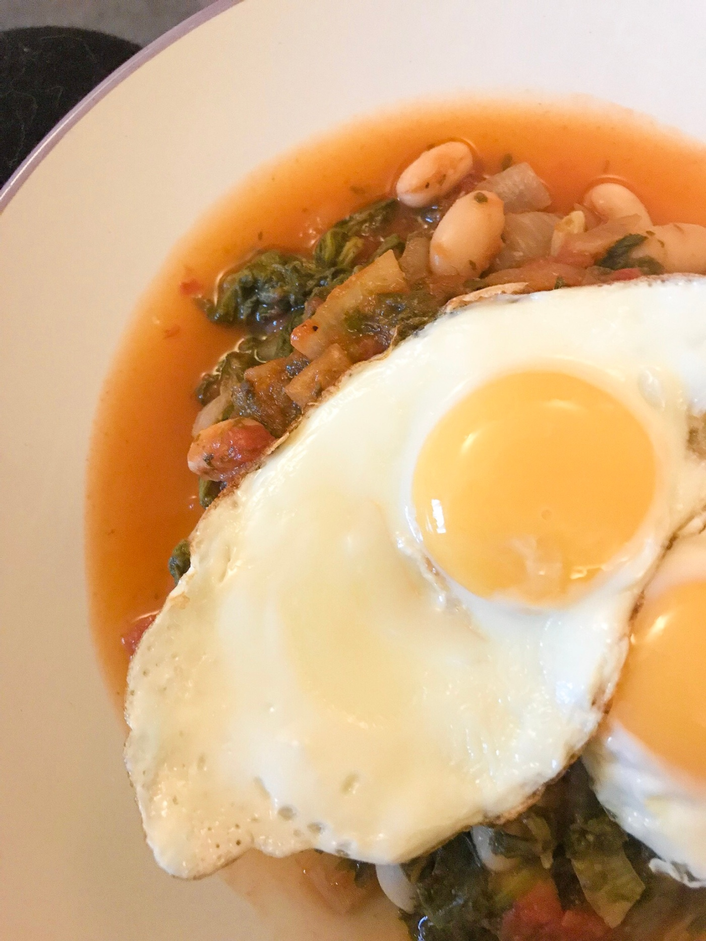 Tomatoes, cannellini beans and spinach topped with fried eggs